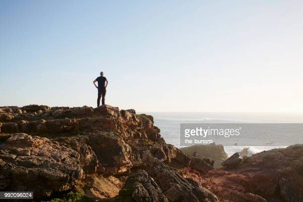 silhouette of man standing on cliff by sea against sky - rocha imagens e fotografias de stock