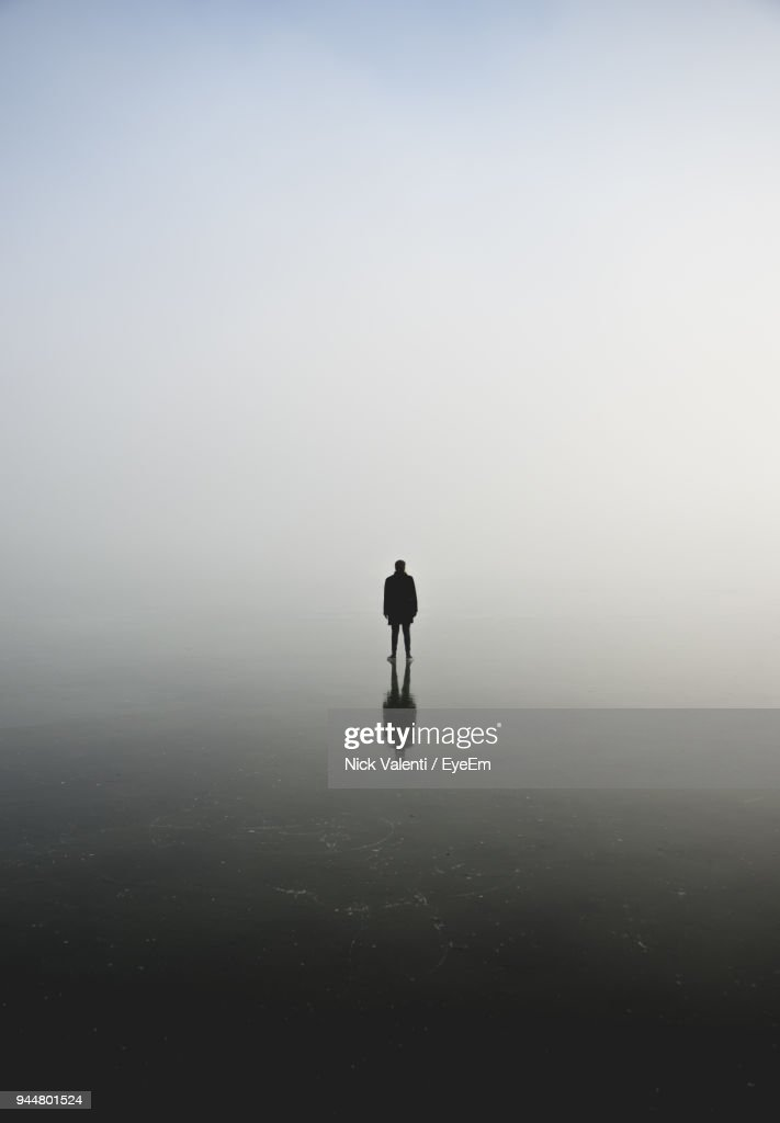 Silhouette Of Man Standing On Frozen Lake Against Sky : Stock Photo
