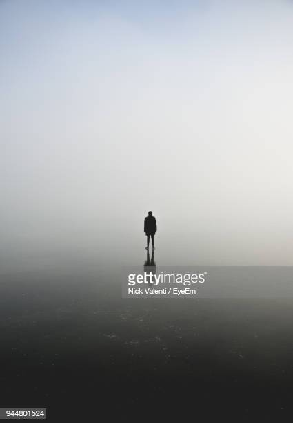 silhouette of man standing on frozen lake against sky - 孤独 ストックフォトと画像