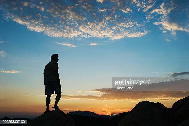 Silhouette of man standing on rock at sunset