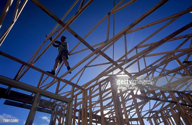 Silhouette of man standing on timber house frame, low angle view