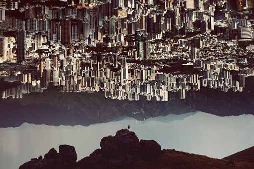 Silhouette of man standing on top of mountain with urban cityscape turning up side down - gettyimageskorea