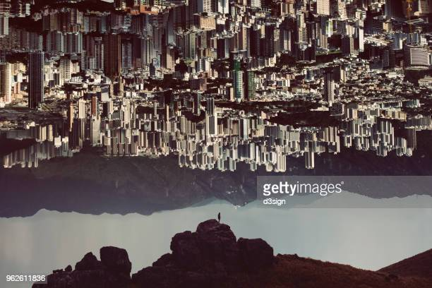 Silhouette of man standing on top of mountain with urban cityscape turning up side down