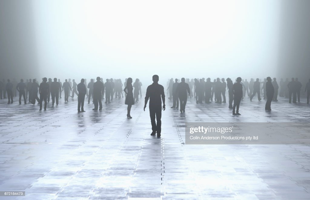 Silhouette of man standing out from the crowd : Stock Photo