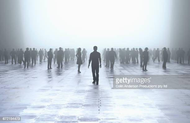 silhouette of man standing out from the crowd - shadow forms stock photos and pictures
