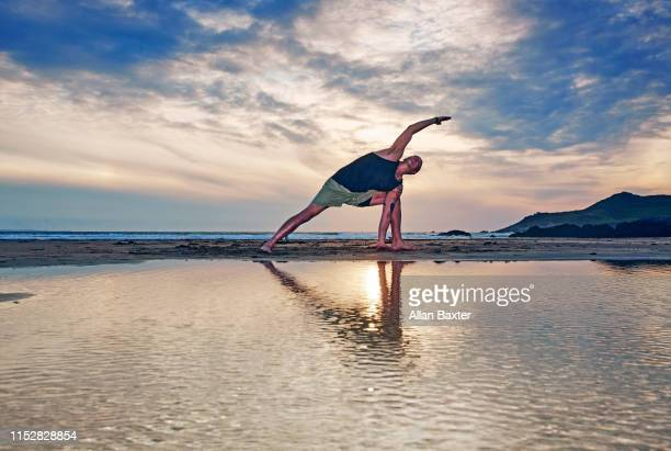 silhouette of man stretching a 'extended side anlge pose yoga move' moves on beach - kung fu yoga stock pictures, royalty-free photos & images