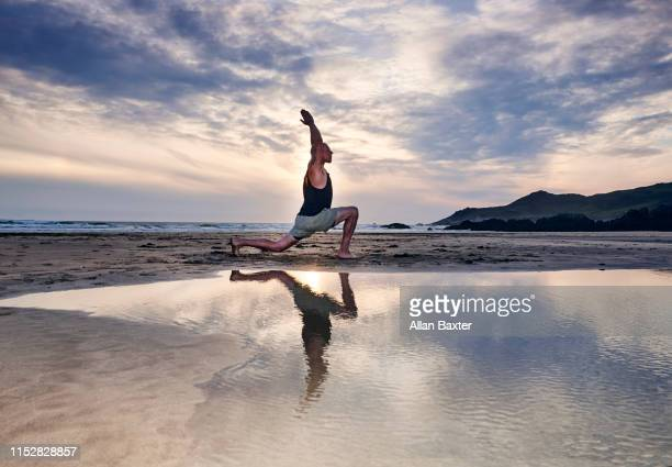 silhouette of man stretching a 'warrior yoga move' moves on beach - yoga stock pictures, royalty-free photos & images