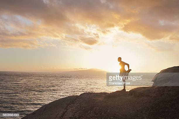 Silhouette of man stretching near ocean, sunset