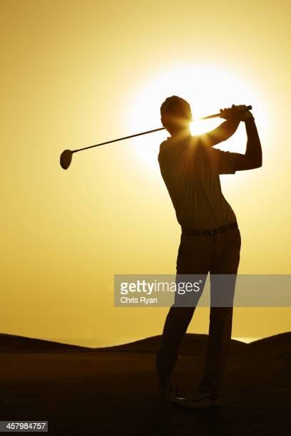 シルエットの男性スインギングゴルフクラブ