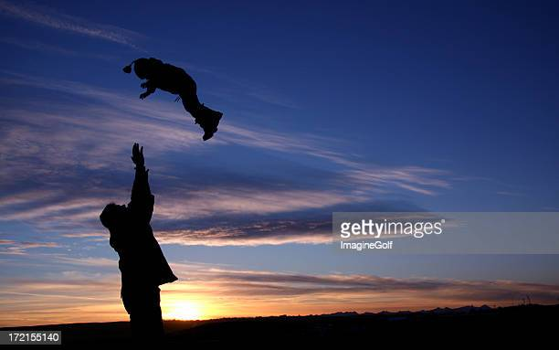 Silhouette of Man Throwing Child in the Air