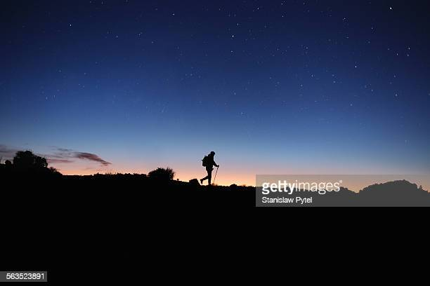 Silhouette of man trekking at night, starry sky