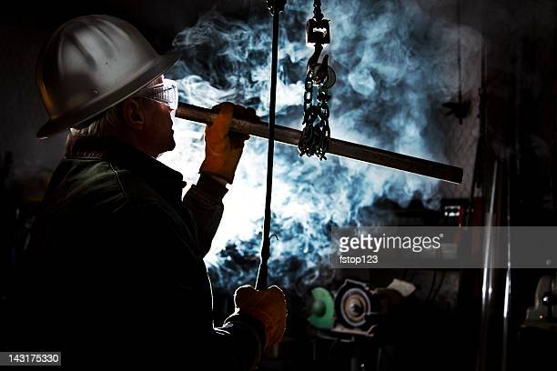 Silhouette of man using chain hoist in workshop.  Steam background