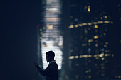 Silhouette of man using smartphone in city