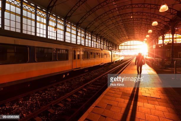 silhouette of man walking on train station platform at sunset - den haag stock-fotos und bilder