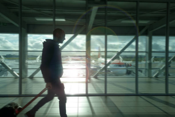 Silhouette of man walking through airport with suitcase