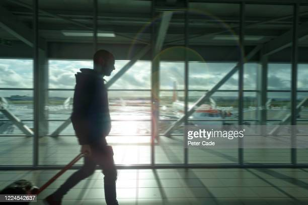 silhouette of man walking through airport with suitcase - arrival stock pictures, royalty-free photos & images