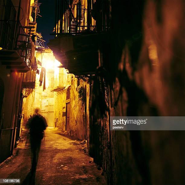Silhouette von einem Mann zu Fuß durch schmale Street