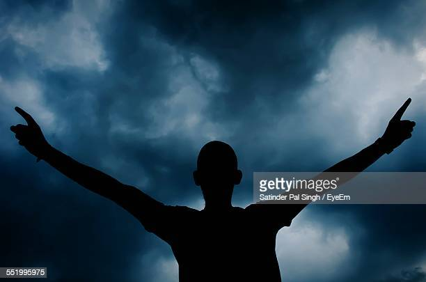 Silhouette Of Man With Arms Outstretched Against Cloudy Sky