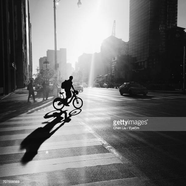 Silhouette Of Man With Bicycle In City