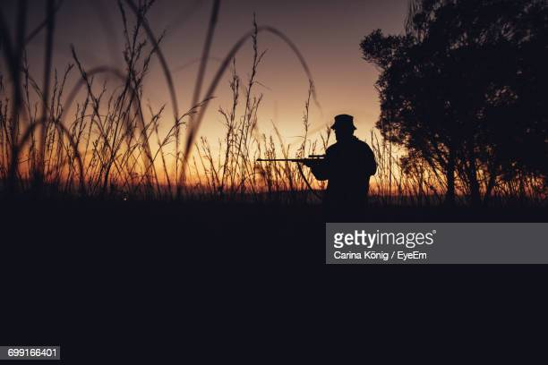 Silhouette Of Man With Gun At Sunset