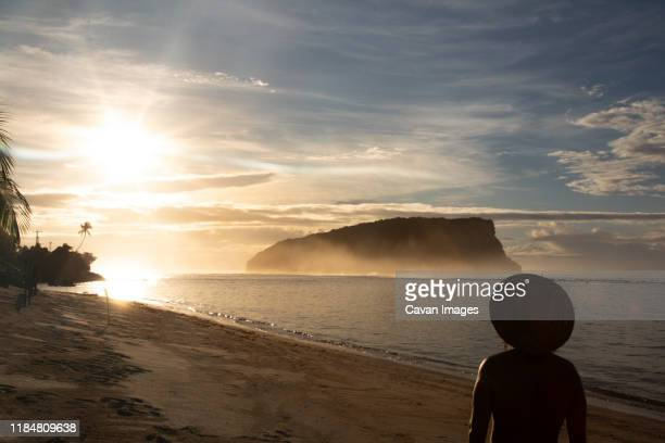 silhouette of man with hat, staring at golden sunrise, at sandy beach - samoa stock pictures, royalty-free photos & images