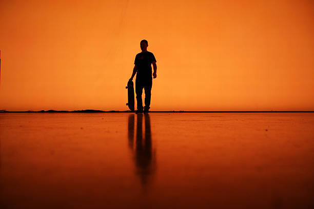 Silhouette of man with skateboard, Berlin