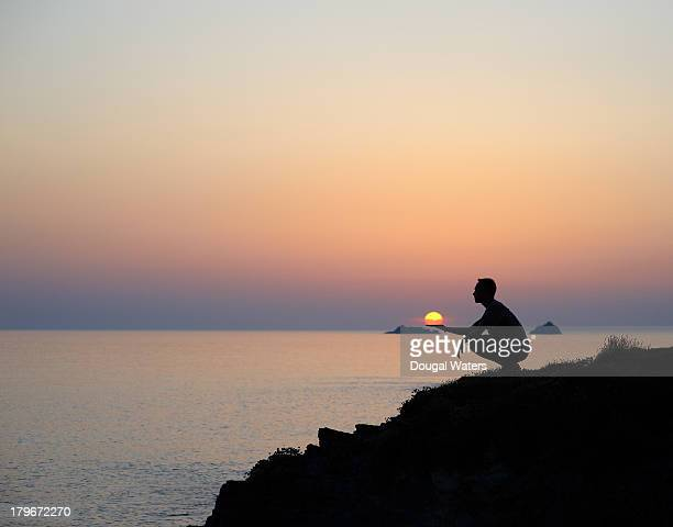 silhouette of man with sun in palm of hand. - dougal waters stock pictures, royalty-free photos & images