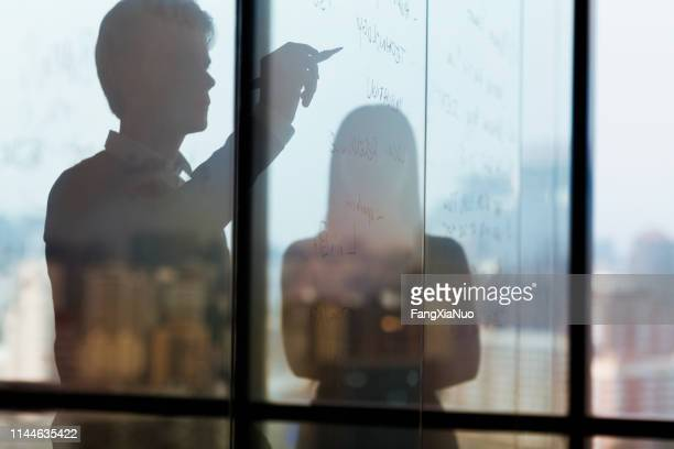 silhouette of man writing ideas on glass wall - business plan stock pictures, royalty-free photos & images