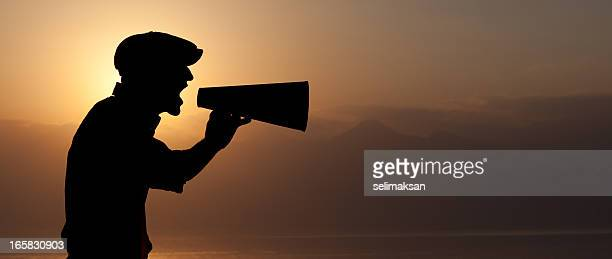 Silhouette of man yelling through a megaphone in sunset
