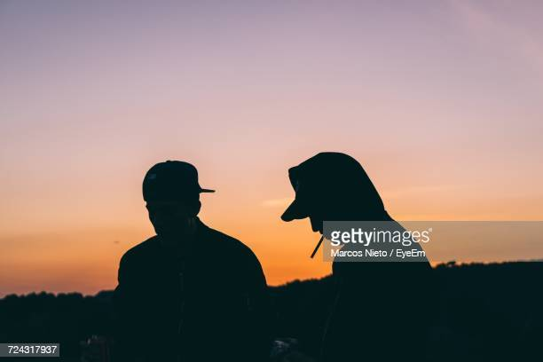 silhouette of men smoking cigarette against sky during sunset - 25 29歳 ストックフォトと画像