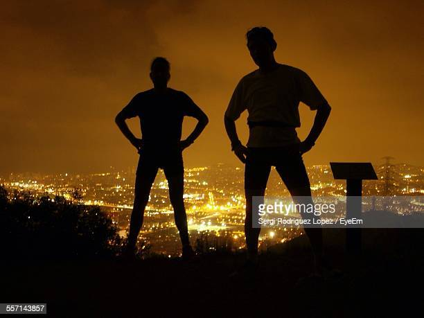 Silhouette Of Men Standing On Hill