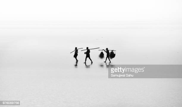 Silhouette of men with sticks and sacks, Chandipur, Odisha, India