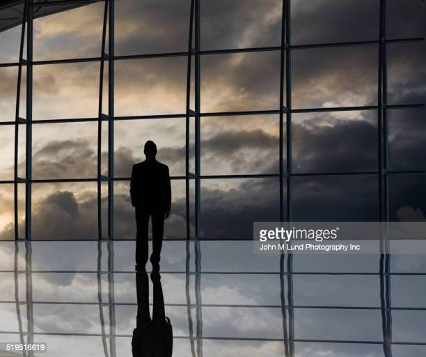 Silhouette of mixed race businessman near window