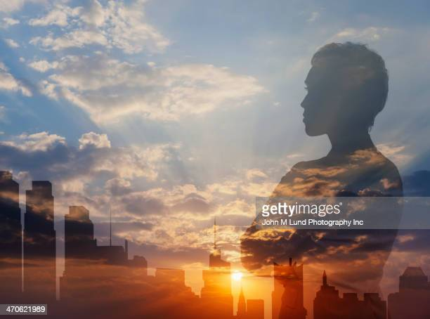 Silhouette of mixed race businesswoman and city skyline