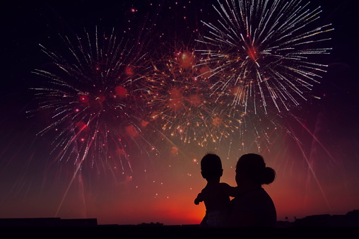 Silhouette of Mother Holding Toddler While Watching Fireworks exploding during Sunset - gettyimageskorea