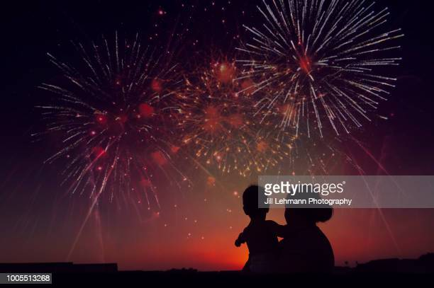 silhouette of mother holding toddler while watching fireworks exploding during sunset - firework display stock pictures, royalty-free photos & images