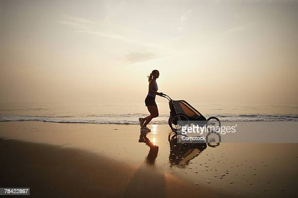 Silhouette of mother jogging on beach with baby stroller