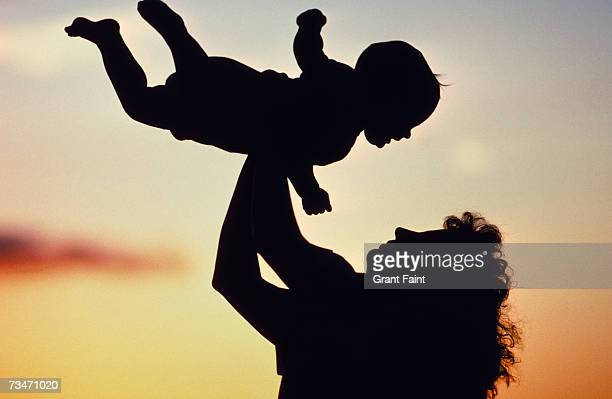Silhouette of mother lifting baby boy (12-15 months)