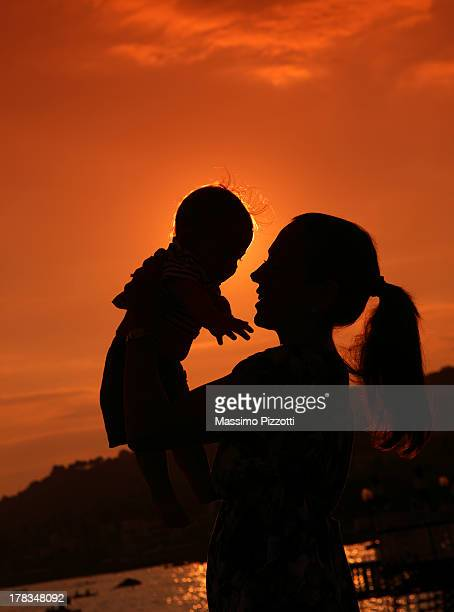 silhouette of mother lifting baby in the air - massimo pizzotti foto e immagini stock