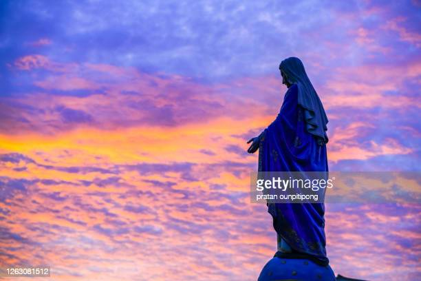 silhouette of mother mary statue against beautiful twilight sky - bible stock pictures, royalty-free photos & images