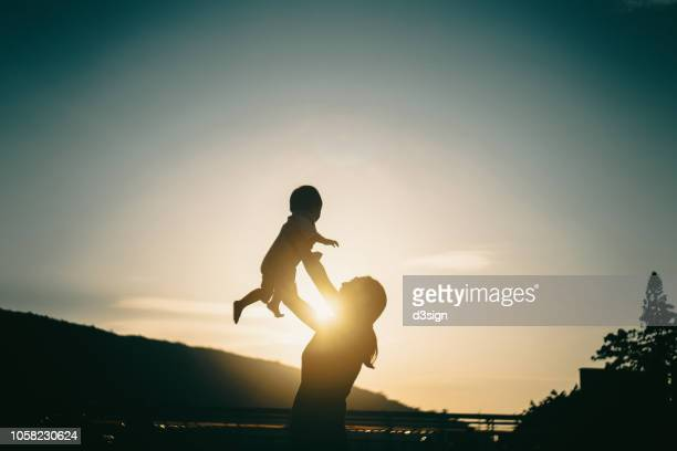 silhouette of mother raising baby girl in the air outdoors against sky during a beautiful sunset - new life stock pictures, royalty-free photos & images