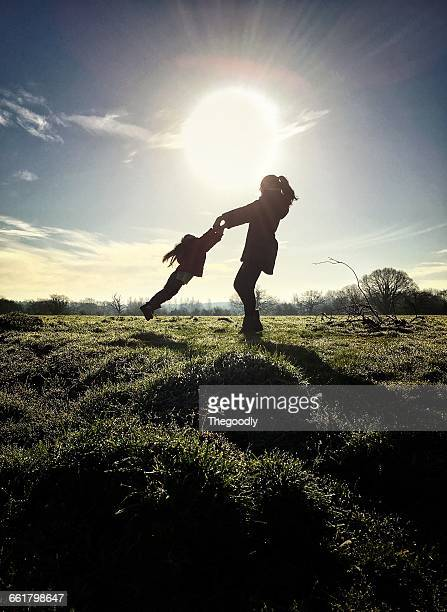 silhouette of mother swinging daughter in field - taken on mobile device stock photos and pictures