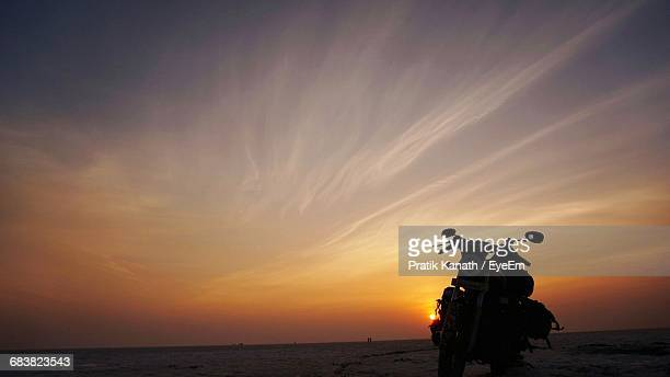 Silhouette Of Motorcycle On Beach At Sunset