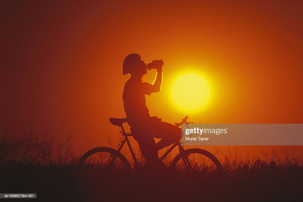 Silhouette of mountain biker drinking from bottle at sunset, side view : Foto stock