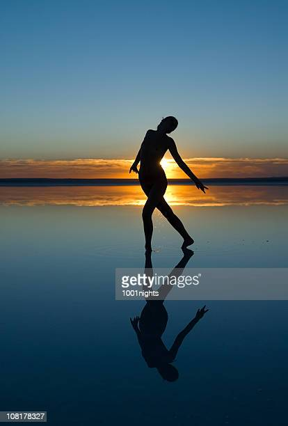 Silhouette of Naked Woman Stepping in Salt Lake at Sunset