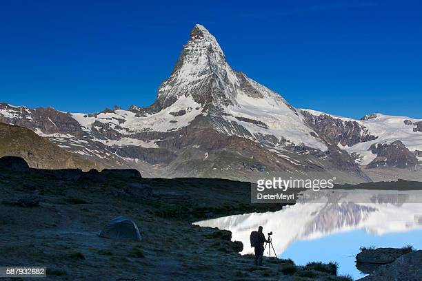 Silhouette of Nature photographer at Matterhorn with Stellisee in foreground