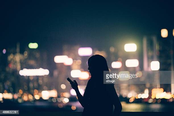 Silhouette of office lady using smartphone in city