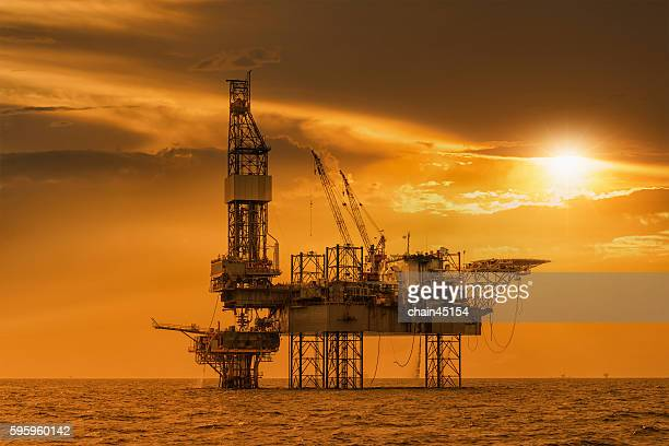 Silhouette of Oil rig (Oil Jack up rig type) that drilling the well to find the fuel energy in oil industry.