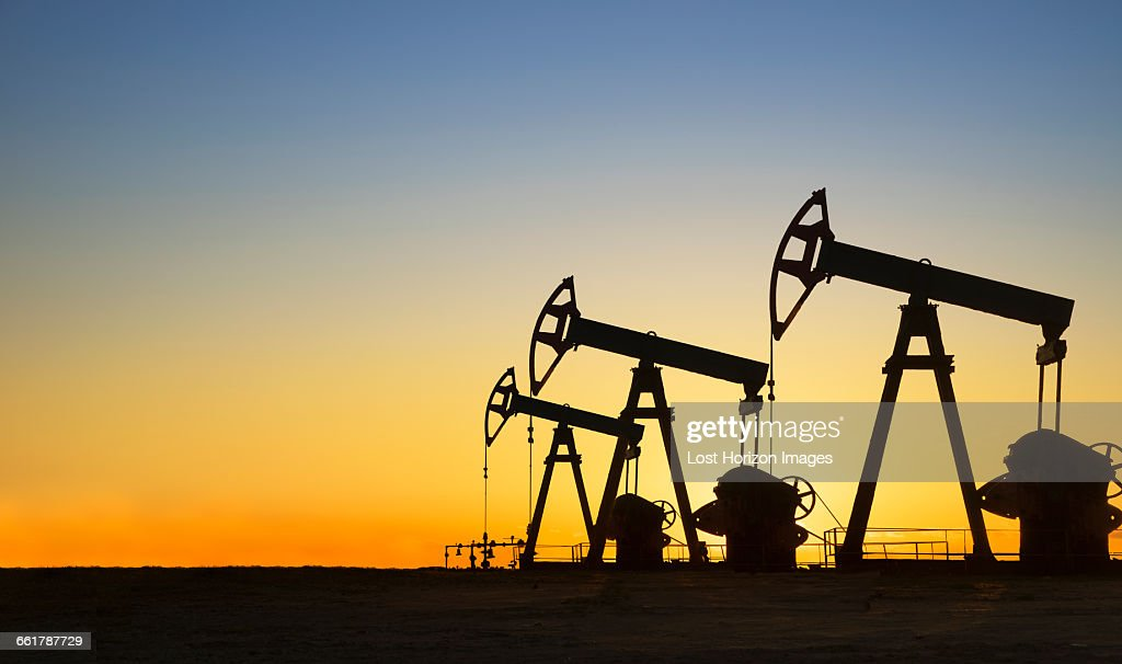 Silhouette of oil wells in desert at sunset, Texas, USA : Stock Photo