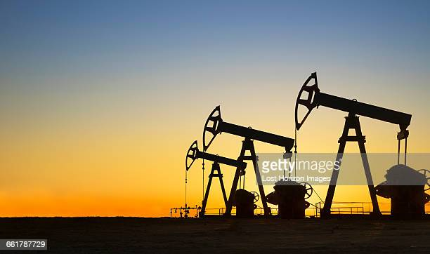Silhouette of oil wells in desert at sunset, Texas, USA